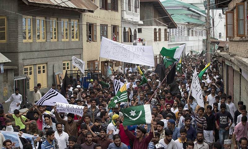 Protesters shout slogans and march on a street after Friday prayers in Srinagar. (Photo: Dar Yasin)